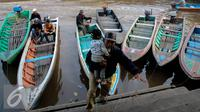 Pria menggendong anaknya turun dari perahu sampan di Sungai Kapuas, Pontianak, Kalimantan Barat, Sabtu (22/8/2015). Perahu Sampan saat ini masih diminati warga sebagai pilihan moda transportasi sederhana di Sungai Kapuas. (Liputan6.com/Faizal Fanani)