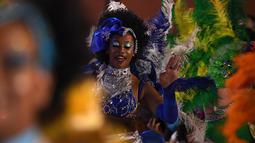 Anggota karnaval Uruguay, Comparsa, menari mengikuti irama musik selama parade karnaval Llamadas di Montevideo, Kamis (7/2). Karnaval terbesar di Uruguay ini menampilkan kelompok penari seksi dan musik tradisional selama dua hari. (PABLO PORCIUNCULA/AFP)