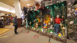 Seorang pria yang mengenakan masker mengamati berbagai dekorasi bertema Halloween di sebuah toko di Mississauga, Ontario, Kanada, pada 29 Oktober 2020. Warga Ontario mulai berbelanja dekorasi dan menghias rumah mereka untuk menyambut Halloween. (Xinhua/Zou Zheng)