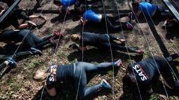 Sejumlah peserta merangkak dibawah kawat berduri saat mengikuti kompetisi Tough Viking di Stockholm, Swedia (12/5). Kompetisi ketangkasan ini dirancang oleh spesialis di Angkatan Bersenjata Swedia. (AFP/Jonathan Nackstrand)