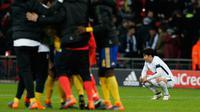 Reaksi striker Tottenham Hotspur, Son Heung-Min setelah kalah atas Juventus pada leg kedua babak 16 besar Liga Champions di Wembley, Kamis (8/3). Gol Heung-Min sia-sia setelah Juventus sanggup mencetak dua gol balasan di paruh kedua. (Glyn KIRK/AFP)