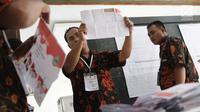 Petugas menunjukkan surat suara saat penghitungan suara Pilkada Jawa Barat 2018 di TPS 06 Nagrak, Gunung Putri, Bogor, Rabu (27/6). TPS tersebut menjadi tempat keluarga besar SBY menunaikan haknya pada Pilgub Jabar 2018. (Liputan6.com/Herman Zakharia)