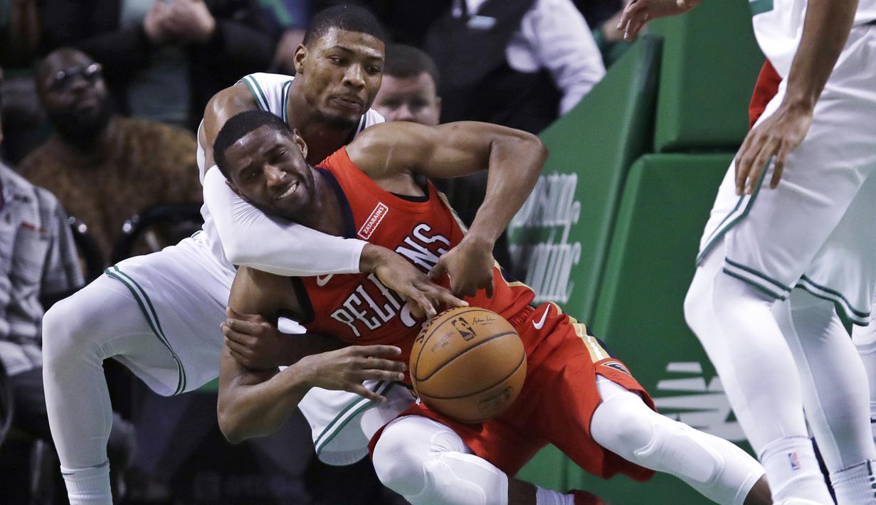 Aksi pemain Boston Celtics, Marcus Smart (kiri) berebut bola dengan pemain New Orleans Pelicans, Ian Clark (2) pada laga NBA basketball game di TD Garden, Boston, (16/1/2018). Celtics kalah 113-116. (AP/Charles Krupa)