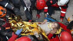 Petugas penyelamat berhasil mengevakuasi Ayda Gezgin, 3, yang terjebak reruntuhan gedung apartemen setelah gempa bumi dahsyat di kota Izmir, Turki, Selasa (3/11/2020). Ayda Gazgin berhasil diselamatkan dari bawah reruntuhan bangunan setelah terkubur selama 4 hari atau sekitar 91 jam. (AFAD via AP)