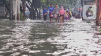 Pejalan kaki melewati banjir yang menggenangi Jalan KH. Ahmad Dahlan Cipondoh, Tangerang, Selasa (16/2/2021). Hujan deras yang melanda wilayah Tangerang mengakibatkan ruas jalan alternatif penghubung Tangerang dengan Jakarta tersebut banjir setinggi lutut orang dewasa. (Liputan6.com/Angga Yuniar)