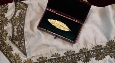 Sebuah rompi dan daun salam emas yang merupakan bagian mahkota dari Kaisar Prancis, Napoleon I diperlihatkan di rumah lelang Osenat di Paris, Prancis (15/11). Kedua benda tersebut akan dilelang di rumah lelang Osenat. (AFP Photo/Stephane De Sakutin)