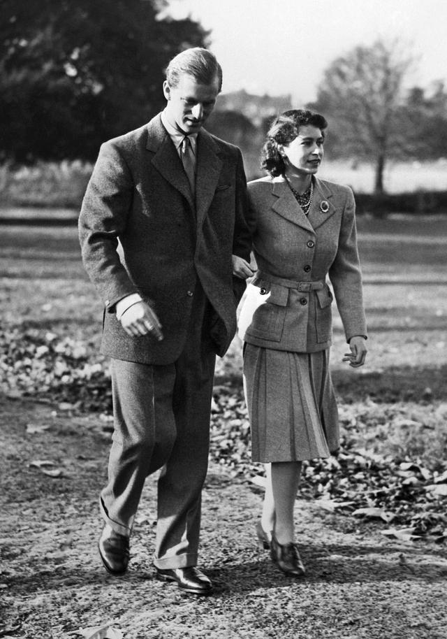 Putri Inggris Elizabeth (calon Ratu Elizabeth II) dan Duke of Edinburgh Pangeran Philip dari Inggris (kiri) berjalan selama bulan madu mereka di perkebunan Broadlands, Hampshire pada 25 November 1947. (AFP)