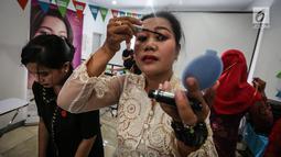 Seorang pengemudi ojek online wanita memakai maskara saat kelas kecantikan jelang peragaan busana di Rawamangun, Jakarta, Jumat (20/4). Kegiatan menyambut Hari Kartini tersebut diikuti puluhan ojek online wanita. (Liputan6.com/Fery Pradolo)
