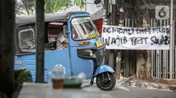Sebuah bajaj melintas di dekat spanduk peringatan untuk pemudik di kawasan Kartini, Sawah Besar, Jakarta, Senin (17/5/2021). Spanduk tersebut untuk memperingati warga yang kembali dari mudik lebaran agar membawa surat bebas COVID-19. (Liputan6.com/Faizal Fanani)