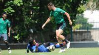 Pemain Timnas Indonesia, Ilija Spasojevic (kanan) mengecoh Muhammad Ridho saat latihan di Lapangan ABC Senayan, Jakarta, Selasa (20/2). Jelang Asian Games 2018, pemain Timnas U-23 kembali melakukan pemusatan latihan. (Liputan6.com/Helmi Fithriansyah)