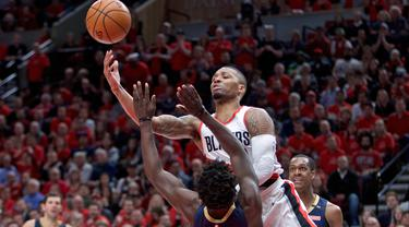 Aksi pemain Blazers, Damian Lillard melakukan tembakan melewati adangan pemain Pelicans, Jrue Holiday pada laga Playoffs game ke-2 NBA basketball di Moda Center, Portland, (17/4/2018). Pelicans menang 111-102. (AP/Craig Mitchelldyer)