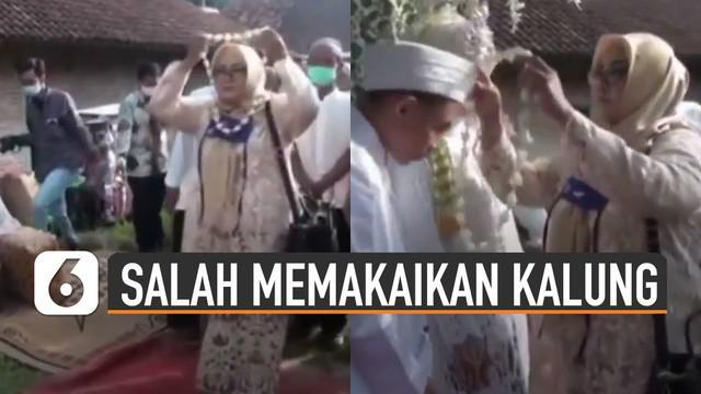 Bukannya memakaikan kalung ke mempelai pria, ibu-ibu ini justru memakai kalung sendiri saat tradisi pernikahan berlangsung.