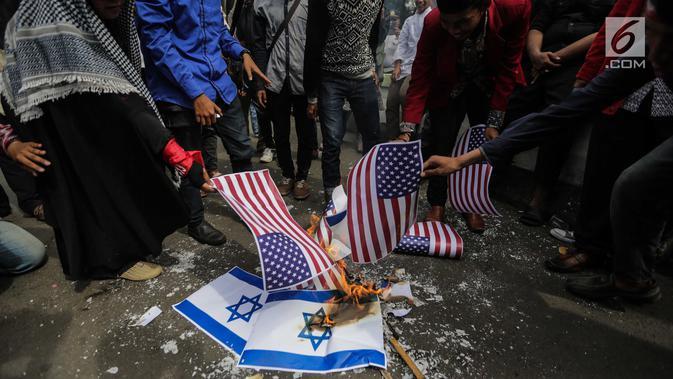 Puluhan massa membakar bendera Amerika Serikat dan Israel dalam Aksi Bela Palestina di depan Kedubes AS, Jakarta, Jumat (15/12). Mereka memprotes sikap Presiden Donald Trump yang mengakui Yerusalem sebagai Ibu Kota Israel. (Liputan6.com/Faizal Fanani)