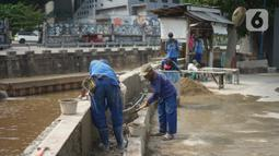 Petugas menyelesaikan proyek peninggian turap Anak Sungai Ciliwung di kawasan Senen, Jakarta, Rabu (4/11/2020). Peninggian turap dilakukan sebagai langkah mengantisipasi banjir yang berasal dari luapan aliran sungai saat hujan deras. (Liputan6.com/Immanuel Antonius)