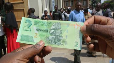 Seorang pria memegang salah satu uang kertas baru yang dikeluarkan Reserve Bank of Zimbabwe di Harare, 12 November 2019. Pemerintah Zimbabwe memperkenalkan kembali mata uang negaranya setelah hampir satu dekade terakhir menggunakan mata uang negara lain untuk bertransaksi. (AP/Tsvangirayi Mukwazhi)
