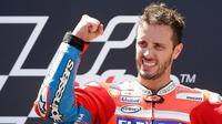 Pembalap Ducati, Andrea Dovizioso merayakan kemenangannya di podium setelah finis pertama pada MotoGP Catalunya di sirkuit Barcelona Catalunya, Minggu (11/6). Ini menjadi gelar juara yang kedua secara beruntun setelah Moto GP Italia. (AP/Manu Fernandez)