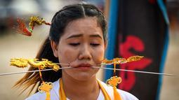 Seorang wanita menusuk pipinya dengan besi  saat mengikuti prosesi perayaan Festival Vegetarian tahunan di Phuket, Thailand, Kamis (3/10/2019). Festival menyiksa diri ini dipercaya bagi warga Phuket akan mendapat kesehatan dan ketenangan pikiran. (AFP Photo/Mladen Antonov)