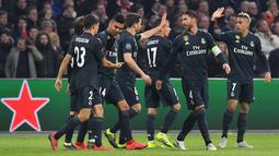Para pemain Real Madrid merayakan gol kedua tim mereka ke gawang Ajax pada leg pertama 16 besar Liga Champions di Johan Cruijff ArenA, Amsterdam, Rabu (13/2). Real Madrid harus bersusah payah menaklukkan Ajax dengan skor tipis 2-1. (EMMANUEL DUNAND/AFP)