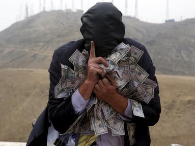 Pria memakai topeng dan membawa uang selama melakukan tetrikal dalam partisipasi mengungkap korupsi di Lima,Peru, (12/11/2015). Acara diselenggarkan oleh organisasi non -pemerintah yang ingin menciptakan kesadaran tentang korupsi. (REUTERS/Mariana Bazo)