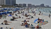 Pengunjung menikmati Clearwater Beach di Florida, Amerika Serikat, Rabu (18/3/2020). Para pengunjung diminta menjaga jarak satu sama lain untuk mengurangi risiko penyebaran virus corona COVID-19. (AP Photo/Chris O'Meara)