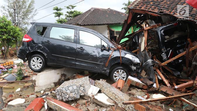 Dua unit mobil tertimbun reruntuhan rumah yang rusak setelah tsunami menerjang kawasan Anyer, Banten, Minggu (23/12). Tsunami menerjang pantai di Selat Sunda, khususnya di daerah Pandenglang, Lampung Selatan, dan Serang. (Liputan6.com/Angga Yuniar)