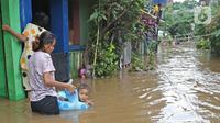Warga beraktivitas di tengah banjir yang melanda kawasan Cipinang Melayu, Jakarta Timur, Jumat (19/2/2021). Banjir di kawasan tersebut akibat curah hujan yang tinggi dan meluapnya air dari Kali Sunter. (Liputan6.com/Herman Zakharia)