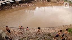 Sejumlah anak bermain di Bantaran sungai Kanal Banjir Barat, Tanah Abang, Jakarta, Sabtu (4/1/2020). Minimnya pengawasan  membuat anak-anak kerap bermain di tempat berbahaya yang berpotensi mengancam keselamatan mereka. (Liputan6.com/Angga Yuniar)