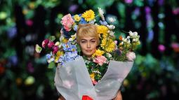 Top model Gigi Hadid mengenakan rancangan rumah mode Moschino saat Milan Fashion Week di Italia, Kamis (21/9). Dalam catwalknya Gigi Hadid mengenakan atribut penuh bunga di tubuhnya. (AFP Photo/Marco Bertorello)