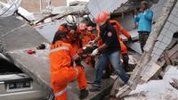 Tim penyelamat membawa korban selamat dari sebuah bangunan restoran yang rusak akibat gempa dan tsunami yang menghantam Palu, Sulawesi Tengah, Minggu (30/9). (AP Photo/Tatan Syuflana, File)