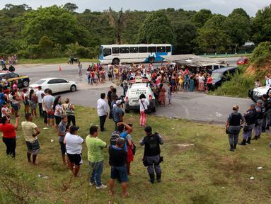 Kerabat dari para narapidana berkumpul di pos pemeriksaan menyusul kerusuhan yang terjadi di dalam penjara kota Amazon, Brasil, Senin (2/1). Setidaknya 60 orang tewas akibat kerusuhan yang dipicu persaingan antargeng narkoba. (REUTERS/Michael Dantas)