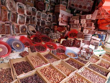 Pedagang kurma menunggu pembeli selama bulan suci Ramadan di sebuah pasar di ibukota Sanaa, Yaman (22/5). (AFP Photo/Mohammed Huwais)