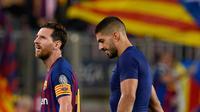 Pemain Barcelona, Lionel Messi dan rekan setimnya, Luis Suarez meninggalkan lapangan usai laga grup B Liga Champions melawan PSV Eindhoven di Camp Nou, Selasa (18/9). Messi tampak membawa bola yang dipakai dalam pertandingan itu pulang. (AFP/Josep LAGO)