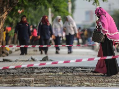 Pejalan kaki melintasi trotoar yang sedang direvitalisasi di kawasan Kramat Raya, Jakarta, Rabu (6/11/2019). Ketua Koalisi Pejalan Kaki Alfred Sitorus menilai pengerjaan revitalisasi trotoar membahayakan pejalan kaki karena tidak ada ruang sementara untuk melintas. (Liputan6.com/Faizal Fanani)