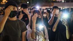 Mahasiswa menutup mata kanan mereka sambil menyalakan ponselnya selama rapat umum di Hong Kong (22/8/2019). para mahasiswa masih ingin memimpin barisan demonstran pro-demokrasi yang hampir setiap hari berada di jalanan untuk memberikan tekanan pada pemerintah. (AFP Photo/Anthony Wallace)
