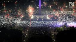 Ribuan warga mengabadikan moment kembang api pada malam pergantian tahun baru 2018 di kawasan silang Monumen Nasional (Monas), Jakarta, Senin (1/1/2018). Monas menjadi salah satu lokasi pilihan warga saat malam tahun baru. (Liputan6.com/Johan Tallo)