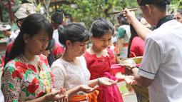Pemuka agama Hindu memberikan air suci untuk sembahyang di Pura Aditya Jaya, Jakarta, Sabtu (17/3). Nyepi dirayakan dengan melakukan kegiatan keagamaan di pura. (Liputan6.com/Herman Zakharia)
