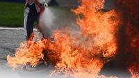 Seorang petugas trek mencoba memadamkan sepeda motor yang terbakar menyusul kecelakaan yang melibatkan pembalap Aprilia Gresini, Lorenzo Savadori dan pembalap KTM, Dani Pedrosa saat balapan MotoGP Styria 2021 di Red Bull Ring, Minggu (8/8/2021). (JOE KLAMAR/AFP)
