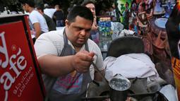 """Seorang anak down syndrome menyiapkan minuman di kedai kopi Sucet  selama festival """"Sham gather us"""" di Damascus, Suriah (11/7). Enam belas anak laki-laki dan perempuan down syndrome bekerja di Cafe Sucet melayani pelanggan. (AFP Photo/Louai Beshara)"""