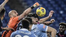 Kiper Lazio, Pepe Reina (kiri), meninju bola dari ancaman pemain Napoli dalam laga lanjutan Liga Italia Serie A 2020/21 pekan ke-13 di Olimpico Stadium, Roma, Minggu (20/12/2020). Lazio mengalahkan Napoli 2-0. (AFP/Filippo Monteforte)