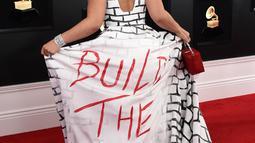 """Penyanyi dan komposer, Joy Villa mengenakan gaun bertuliskan """"Build the Wall"""" pada perhelatan Grammy Awards 2019 di Los Angeles, Minggu (10/2). Joy Villa memakai dress yang terinspirasi tembok perbatasan antara AS dan Meksiko. (Jordan Strauss/Invision/AP)"""