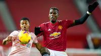 Gelandang Manchester United, Paul Pogba, berebut bola dengan pemain Sheffield United, Ethan Ampadu, pada laga Liga Inggris di Stadion Old Trafford,  Kamis (28/1/2021). MU takluk dengan  skor 1-2. (AP/Tim Keeton,Pool)