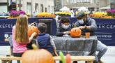 Warga New York mengukir labu dalam persiapan Halloween di Rockefeller Center (22/10/2020). Para pekerja di Rockefeller Center beristirahat sejenak untuk mempelajari cara mengukir labu dengan benar dari Maniac Pumpkin Carvers, seniman dari Brooklyn . (Diane Bondareff/AP Images for Tishman Speyer)