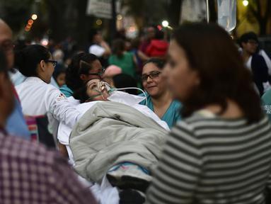 Seorang pasien dievakuasi dari sebuah rumah sakit saat terjadi gempa kuat di Mexico City, Meksiko (16/2). Gempa bumi berkekuatan 7,2 Skala Richter (SR) mengguncang Meksiko. (AFP Photo/Pedro Pardo)