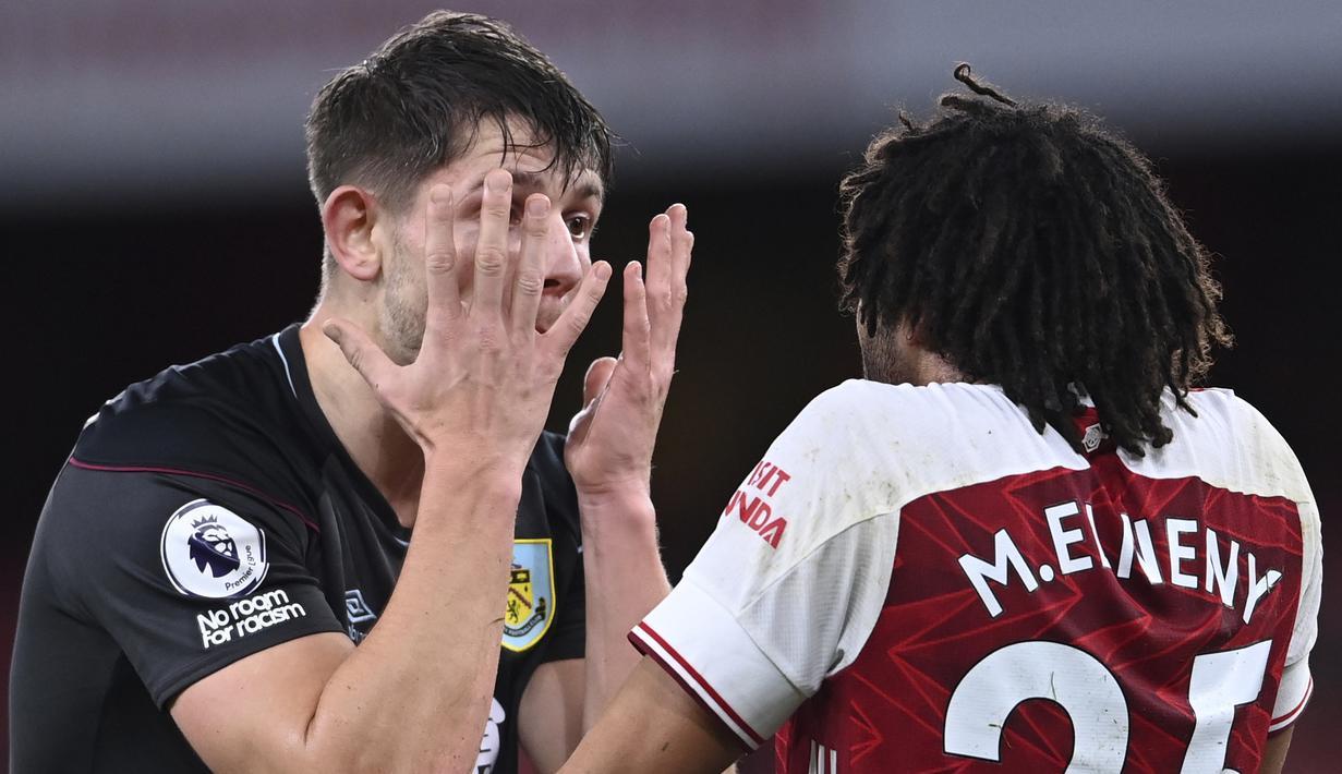 Pemain Burnley,James Tarkowski (kiri) melakukan adu argumentasi dengan pemain Arsenal, Mohamed Elneny dalam pertandingan Liga Inggris. (Foto: AP/Pool/Laurence Griffiths)