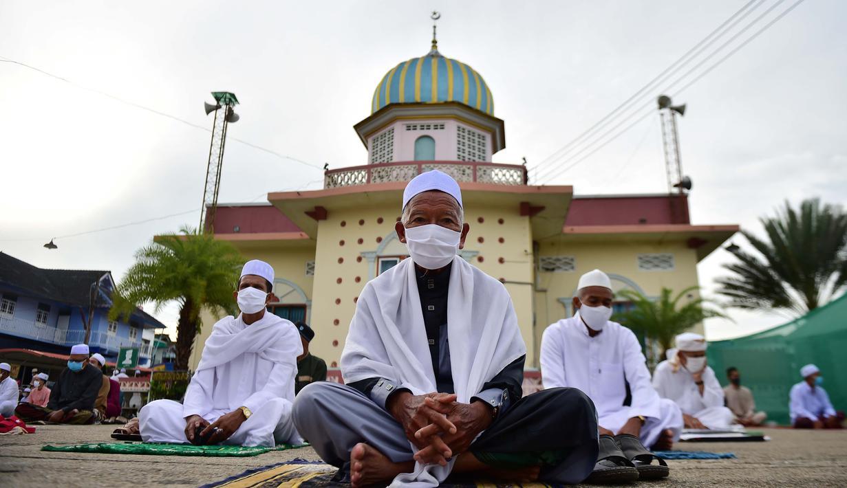 Pria-pria Muslim mengenakan masker dan duduk dengan menjaga jarak untuk melaksanakan salat berjemaah pada Idul Fitri yang menandai akhir bulan suci Ramadhandi halaman masjid Yakaniah di Narathiwat, provinsi selatan Thailand, 24 Mei 2020. (Photo by Madaree TOHLALA / AFP)