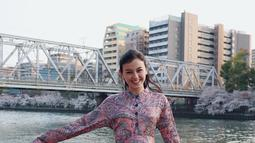 Masih di Jepang, Kimberly terlihat sangat feminin memakai baju berwarna pink gelap bercorak. Dengan latar sungai di belakangnya, senyuman manisnya tak pernah pudar. (Liputan6.com/IG/kimbrlyryder)