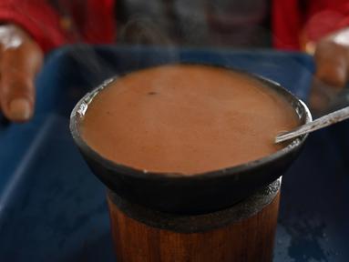 Seorang pria membawa kopi Kawa Daun di sebuah kafe tradisional di Tabek, Sumatera Barat (29/11).  Keunikan kopi di daerah ini adalah minuman yang mengekstrak rasa dari daun tanaman daripada kacangnya. (AFP Photo/Adek Berry)