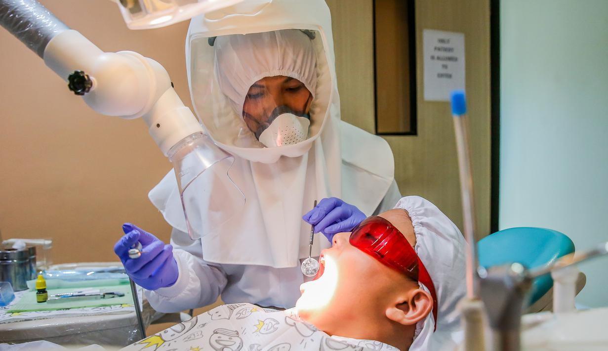 """Dr. Maureen P. Ines-Manzano, seorang dokter gigi, memeriksa pasiennya di dalam kliniknya di Manila, Filipina, pada 19 Oktober 2020. Pasien Dr. Manzano menjulukinya """"dokter gigi astronaut"""" karena mengenakan setelan PAPR untuk melindungi pasien dan dirinya dari COVID-19. (Xinhua/Rouelle Umali)"""