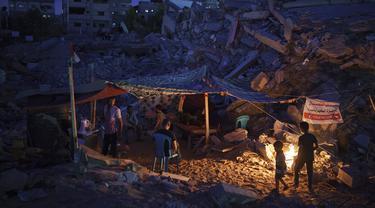 Warga Palestina duduk dalam tenda darurat yang dibangun di antara puing-puing rumah mereka yang hancur karena serangan udara Israel di Beit Lahia, Jalur Gaza, Jumat (4/6/2021). Gencatan senjata yang mengakhiri perang 11 hari antara Hamas dan Israel telah lama dilakukan. (AP Photo/Felipe Dana)