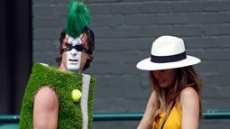 Penonton mengenakan kostum lapangan tenis tiba untuk mengambil tempat duduk selama turnamen tenis Wimbledon 2019 hari ke tujuh di The All England Tennis Club, London (2/7/2019). (AP Photo/Alastair Grant)
